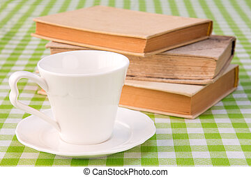 Cup with books on the table.