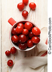Cup with cherry and towel on white wooden background, top view