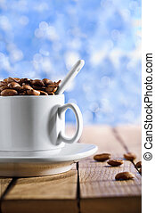 cup with coffee beans on the wooden table