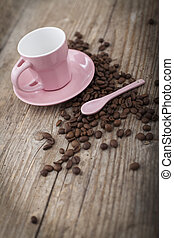 Cup with coffee beans on wooden surface