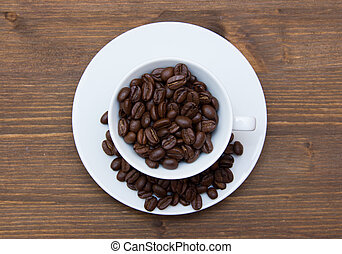 Cup with coffee beans on wooden table top view