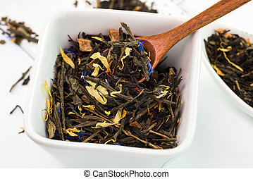 Cup with dry green tea leafs.
