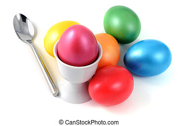 Cup with easter eggs and spoon on white isolated background