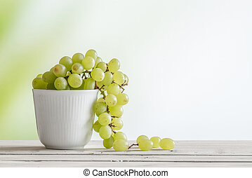 Cup with green grapes