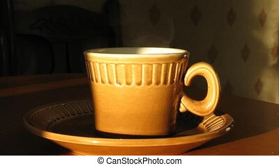 Cup with hot coffee on saucer. Time lapse. Moving shadow.