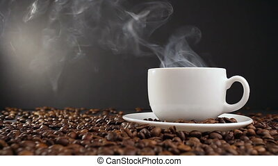 cup with hot drink on roasted coffee beans. dolly shot.