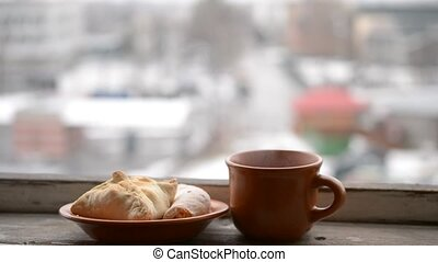 Cup with hot drink steaming and buns on saucer