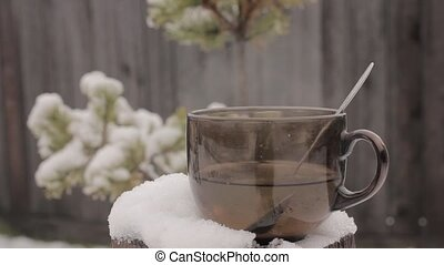 cup with hot tea on a snow-covered stump, on a fence and spruce branch backdrop