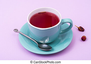 Cup with red tea on pink background