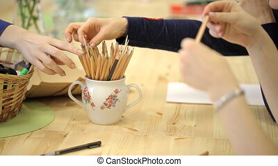 Cup with set of pencil on table, women take it, start to work. On table is empty sheet of paper