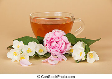 Cup with tea, branches of jasmine and rose