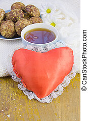 cup with tea, cakes and red heart