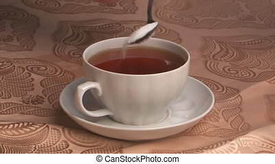 To fill granulated sugar in a cup of tea and stirring by its teaspoon.