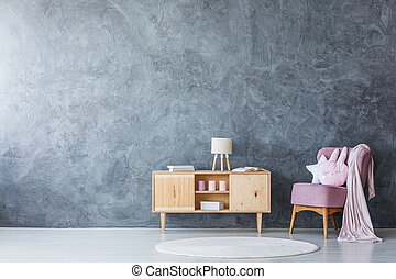 Cupboard and armchair on empty wall