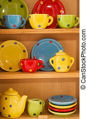 Cupboard with cheerful crockery - wooden cupboard with...
