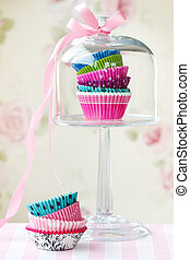 Colorful cupcake cases in a domed cupcake stand