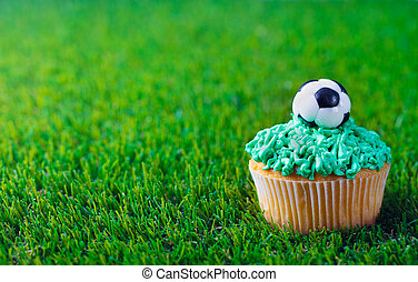 Cupcake decorated with football ball on green grass background. Copy space.