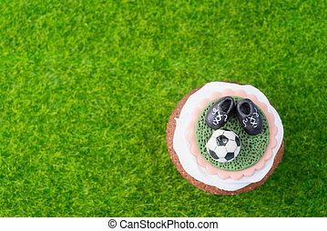 Cupcake in football style on green grass - top view