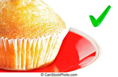 Cupcake on a plate, with a focus on the check mark.