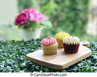 Cupcake on wooden board and green nature blurred background
