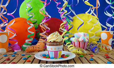 cupcake, på, rustik, trä tabell, med, bakgrund, av, färgrika ballonger, plast kopp, och, candies, med, blå vägg, in, bakgrund