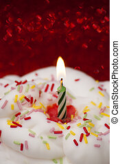 Cupcake with a lit candle over bright red background