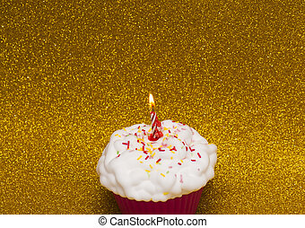 Cupcake with a lit candle over bright background