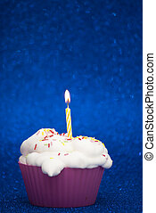 Cupcake with a lit candle over bright blue background