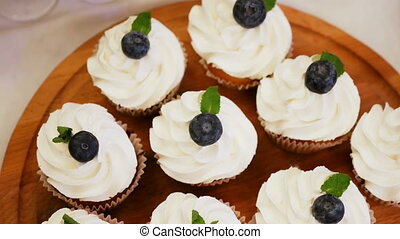 cupcake with cream and blueberries on top standing on a...