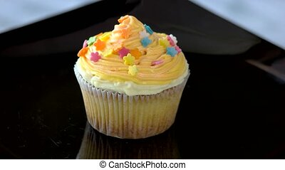 Cupcake with delicate orange cream. Small decorated cake on...
