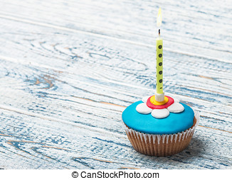 Cupcake with floral decorations and a burning candle