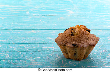 Cupcake with raisins on blue background