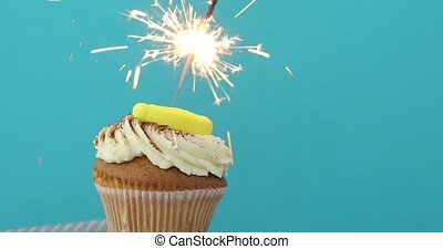 Cupcake with sprinkles and sparkler blue background - Yellow...