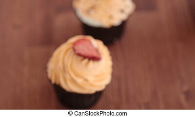 cupcake with strawberries on wooden table