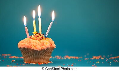 Cupcake with the 4 burning festive candle on a blue background