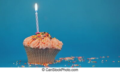 Cupcake with the burning festive candle on a blue background