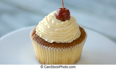 Cupcake with vanilla topping on plate. Yummy cake with ...