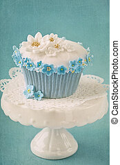 Cupcake with white and blue flowers