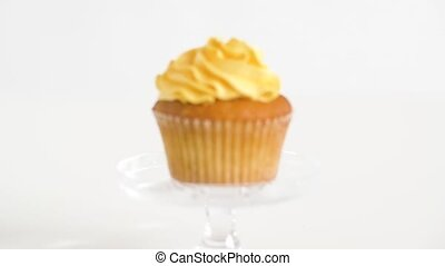 cupcake with yellow frosting on glass stand