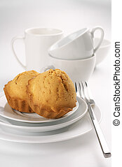 Two homemade cupcakes and white dishware on light background.