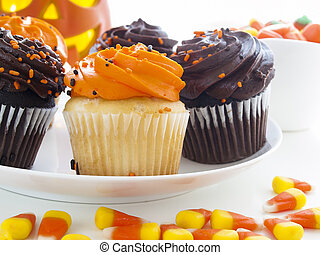 Halloween cupcakes with orange and black icing on white plate.