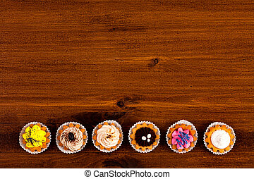 Cupcakes on a brown wooden table, top view