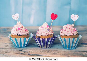 Cupcakes - Photo of 3 cupcakes on wooden background