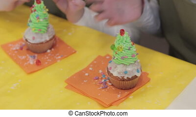 Cupcakes. Two little girls decorate muffins