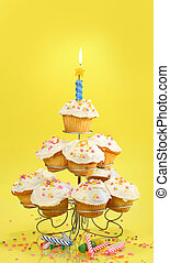 Cupcakes with blue candle on yellow - Cupcakes on...