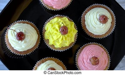 Cupcakes with cream cheese frosting. Small colorful...