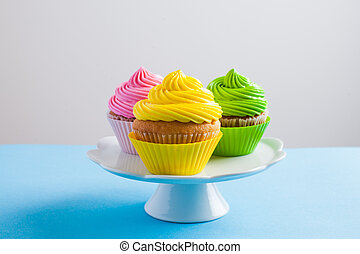 Cupcakes with cream cheese on the white cake stand