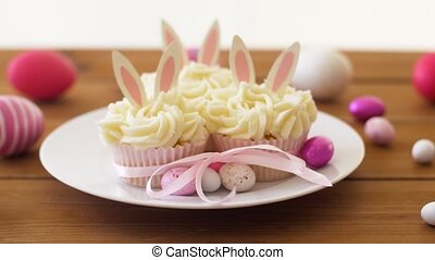 cupcakes with easter eggs and candies on table - easter,...