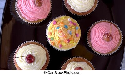 Cupcakes with icing. Small appetizing desserts with cherry...
