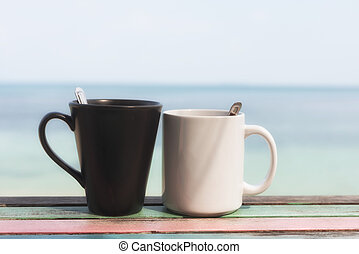 Cuple of coffee cups in the morning on retro terrace facing seascape